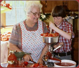 Grandmother grinding tomatoes with grandson